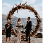 wedding ceremony in front of a lake, with a man and woman holding hands, celebrant standing to one side