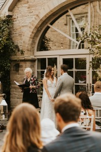 wedding ceremony taking place outdoors with a man and woman and their celebrant, with guests seated in front of them
