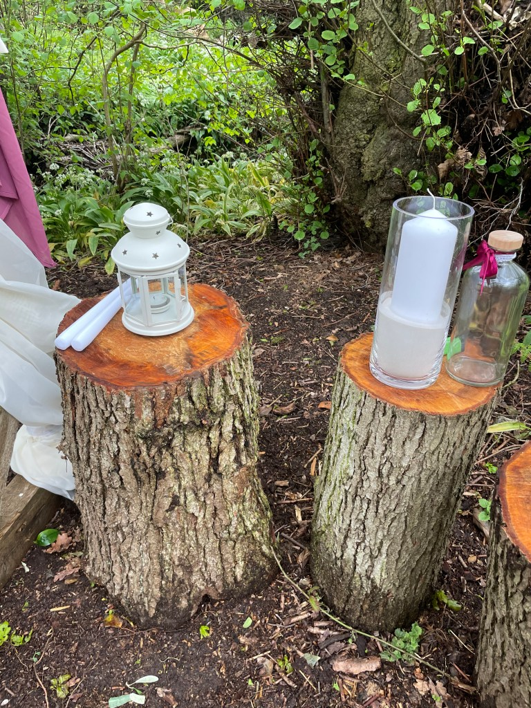 two blocks of wood with a lantern on one block and a candle on the other in a woodland area ready for a wedding ceremony
