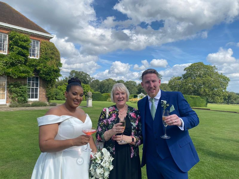 celebrant and bride and groom stand with champagne glasses in a lovely hotel and manor house in Hertfordshire
