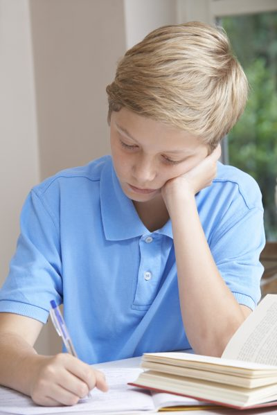 Boy At Home Finding Homework Difficult