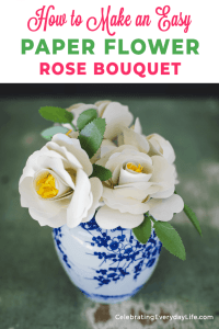 white paper roses in a blue and white vase on a green table
