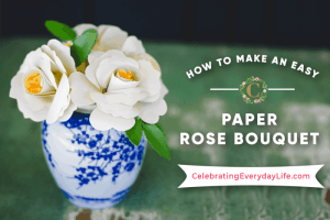 white paper rose in a blue and white vase sitting on a green wood table