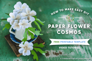 easy DIY white paper flowers with green leaves in a white vase sitting on a green table