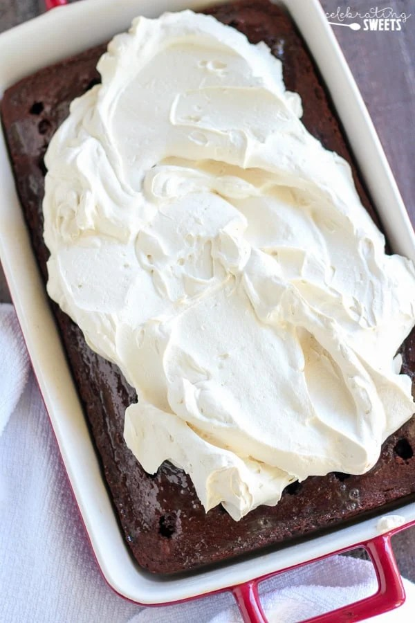Mocha Poke Cake - A chocolate and coffee flavored cake that is poked, drenched with a creamy mocha filling, and finished with espresso whipped cream.