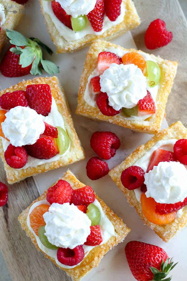 Mini Cream Cheese Fruit Tarts- A puff pastry tart shell filled with a no-bake lemon cream cheese filling and topped with fresh fruit andwhipped cream.