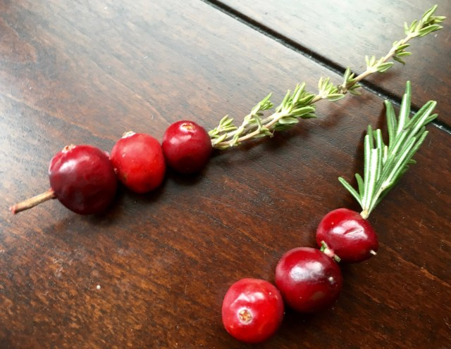 Thread fresh cranberries on rosemary stem for a festive holiday drink garnish.