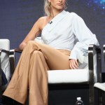 Hailey Baldwin speaks onstage at the 2017 Summer Television Critics Association Press Tour about 'TBS Drop the Mic,' of which she is the host. She is wearing a Jonathan Simkhai One Shoulder Jumpsuit in Khaki/French Blue Pinstripe.