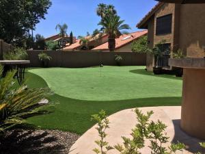 private backyard landscaped with artificial grass putting green