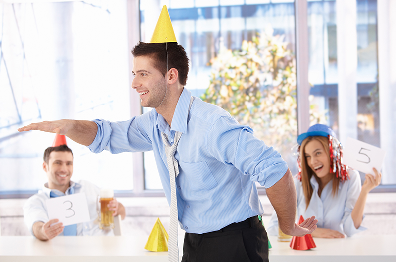 A silly office party with a man and a cone on his head.