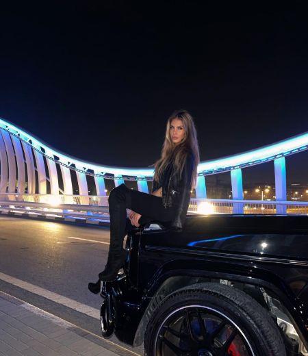 Adixia posing with a car in Dubai
