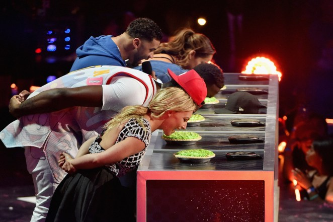 Host Russell Wilson (top) cheers on as professional snowboarder Jamie Anderson and other athletes participate in a key slime pie eating contest onstage during the Nickelodeon Kids' Choice Sports Awards 2016 at UCLA's Pauley Pavilion on July 14, 2016 in Westwood, California. Photo: Dave Mangels/Getty Images