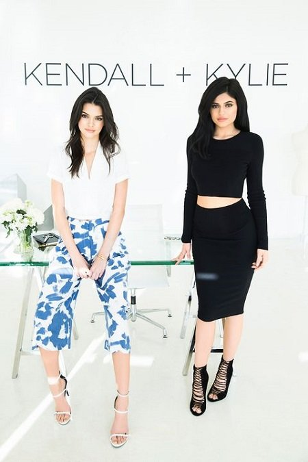Kylie (right) and Kendall Jenner (left) posing for their line 'Kendall + Kylie' written above them.