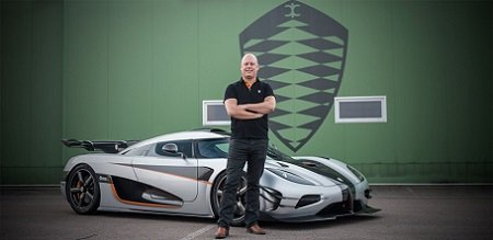 Christian von Koenigsegg in standing in front of his Agera RS folding arms and the brand logo behind him on a green background.
