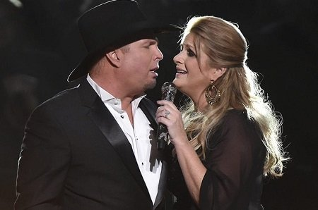 Garth Brooks and Trisha Yearwood facing each other and singing together.