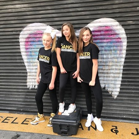Maddie Ziegler, Mackenzie Ziegler and JoJo Siwa posing for Cancer awareness.