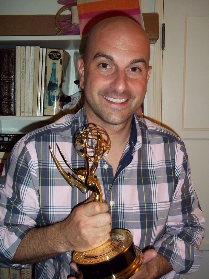 Edward Lawrence holding his Emmy award and smiling at the camera.
