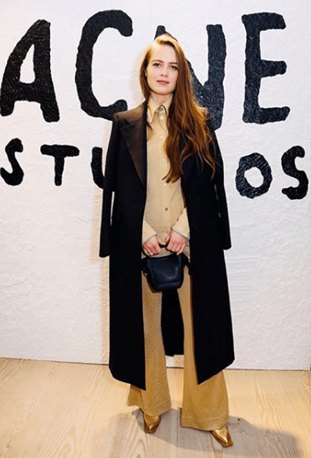 Hera Hilmar standing in front of Acne Studios logo and after she appeared in the show SEE