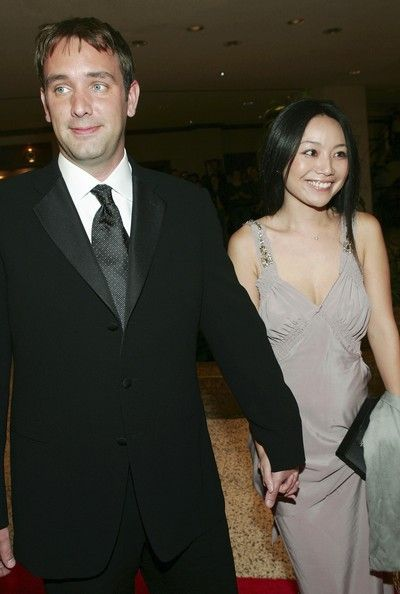 Trey (left) holding Emma's hand while wearing a suit and Emma is in a light drey revealing dress.