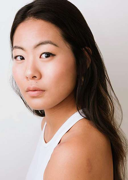 Nicole Kang is looks into the camera, wearing a white dress.