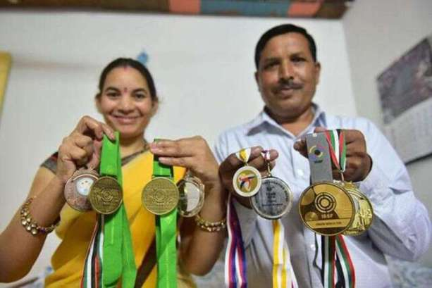 Chinki Yadav's parents showing the medals won by Chinki