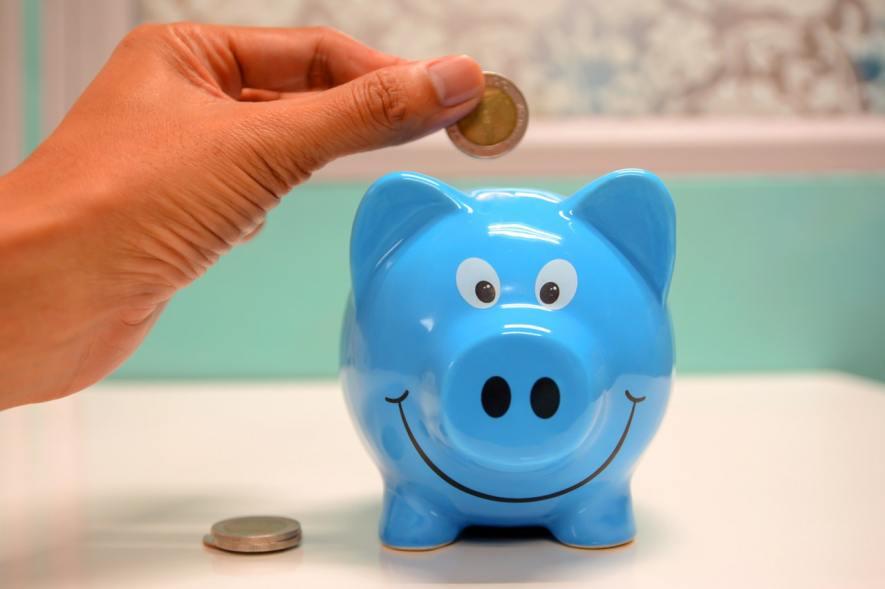 Um cofre azul no formato de um porquinho sobre uma mesa e uma mão feminina insere moedas