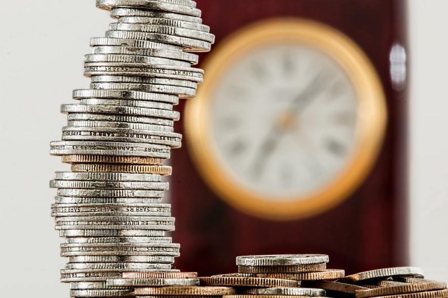Relógio na parede desfocado com um molho de moedas à sua frente indicando a necessidade de fazer gestão financeira