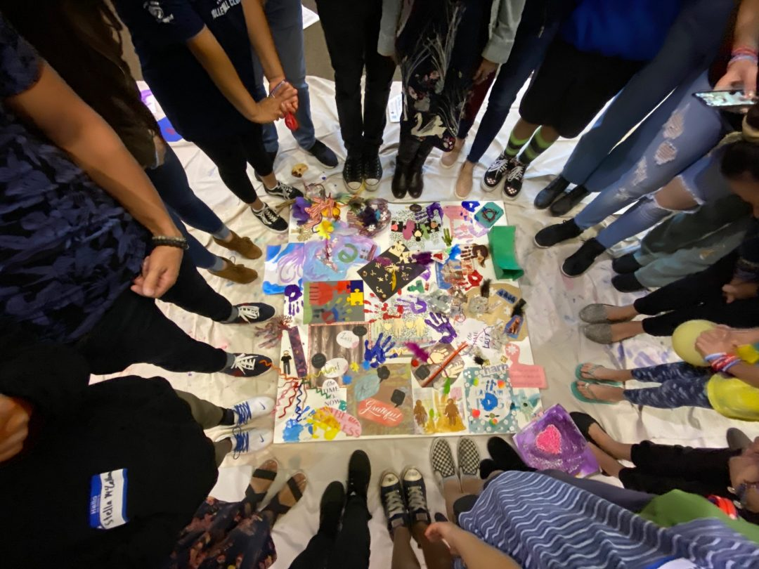 photo looking down on square colorful painting on floor surrounded by circle of young people