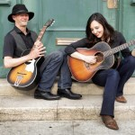 photo of Don Logsdon and Jenni Alpert playing guitars on porch steps