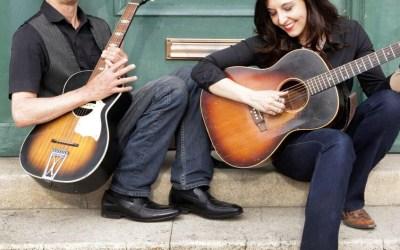 photo of Don Logsdon and Jenni Alpert playing guitars on porch steps
