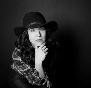 photo of singer-songwriter Jenni Alpert posing in black cowboy hat