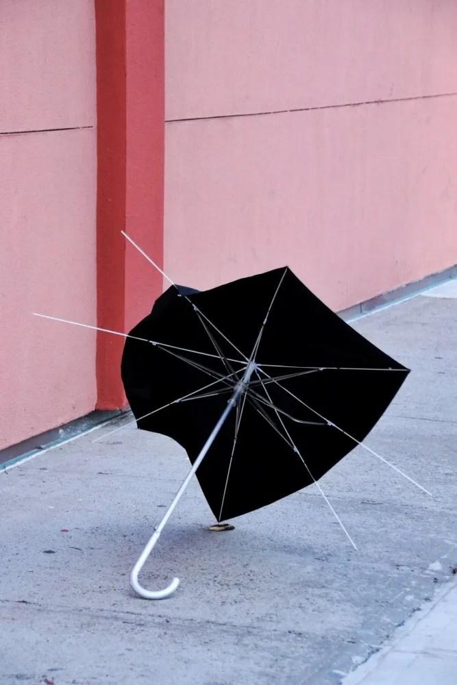 parapluie cassé sur un trottoir et mur rose
