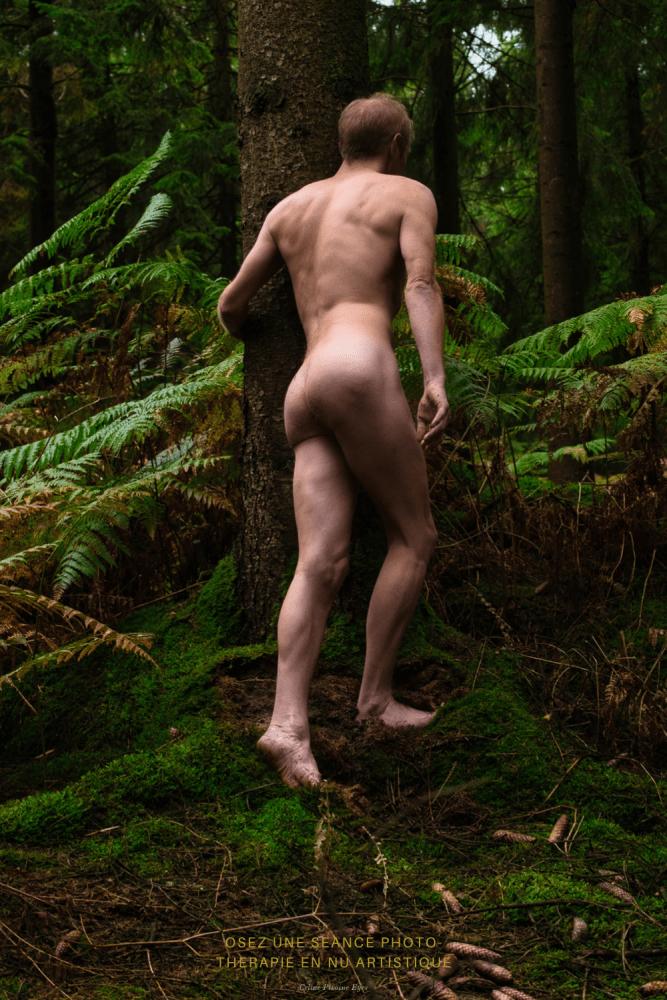 Homme nu sur un arbre en forêt en automne