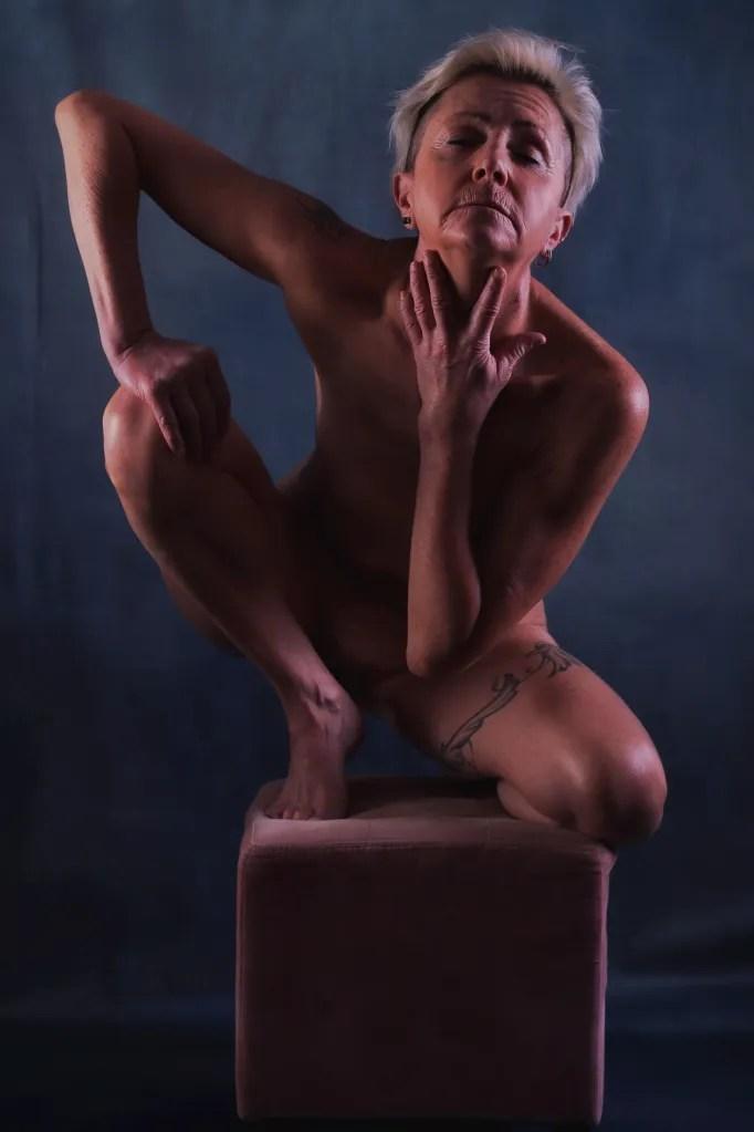 Femme mature en nu artistique accroupie sur un tabouret en clair obscur les yeux fermés