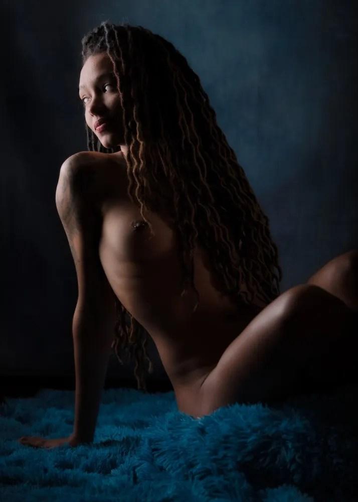 Femme black en nu artistique de profil assise sur un tapis bleu cheveux longs dreadlock