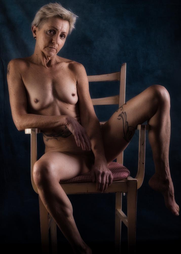 Femme mature tatouée en nu artistique assise sur une chaise les jambes écartées