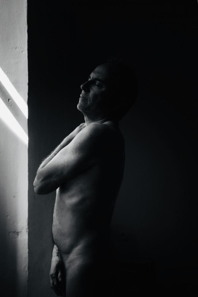 Homme en nu artistique et clair obscur de profil debout devant une fenêtre