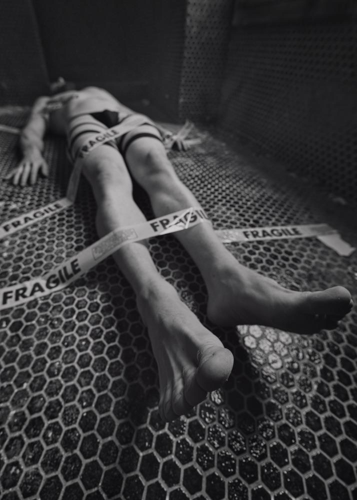 Homme nu allongé sur un sol carrelé noir scotché avec le mot fragile