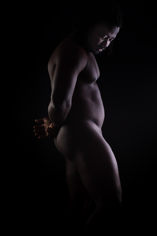 homme black noir en nu artistique clair obscur debout de profil les mains derrière le dos et la tête baissée
