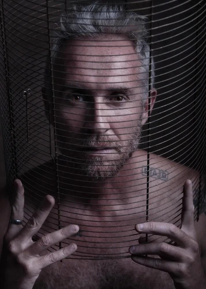 portrait homme nu en cage cheveux blanc et barbu tatoué