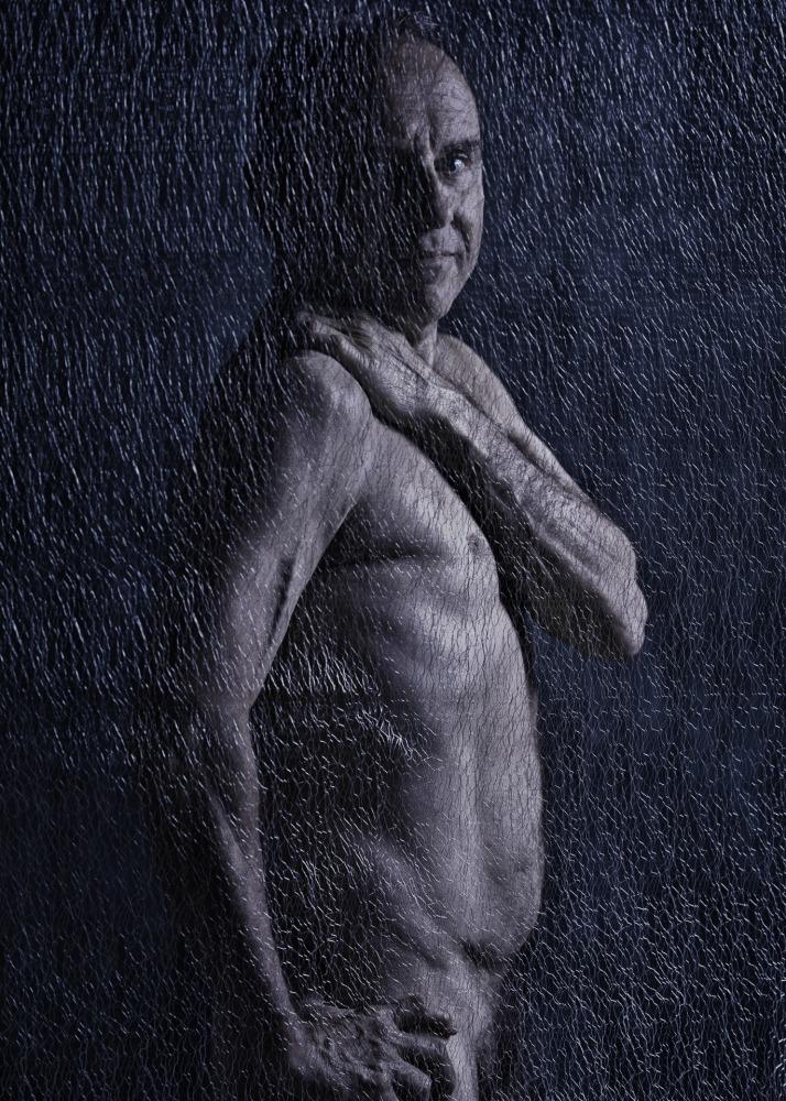 Homme de profil en nu artistique derrière un tissu transparent en clair obscur