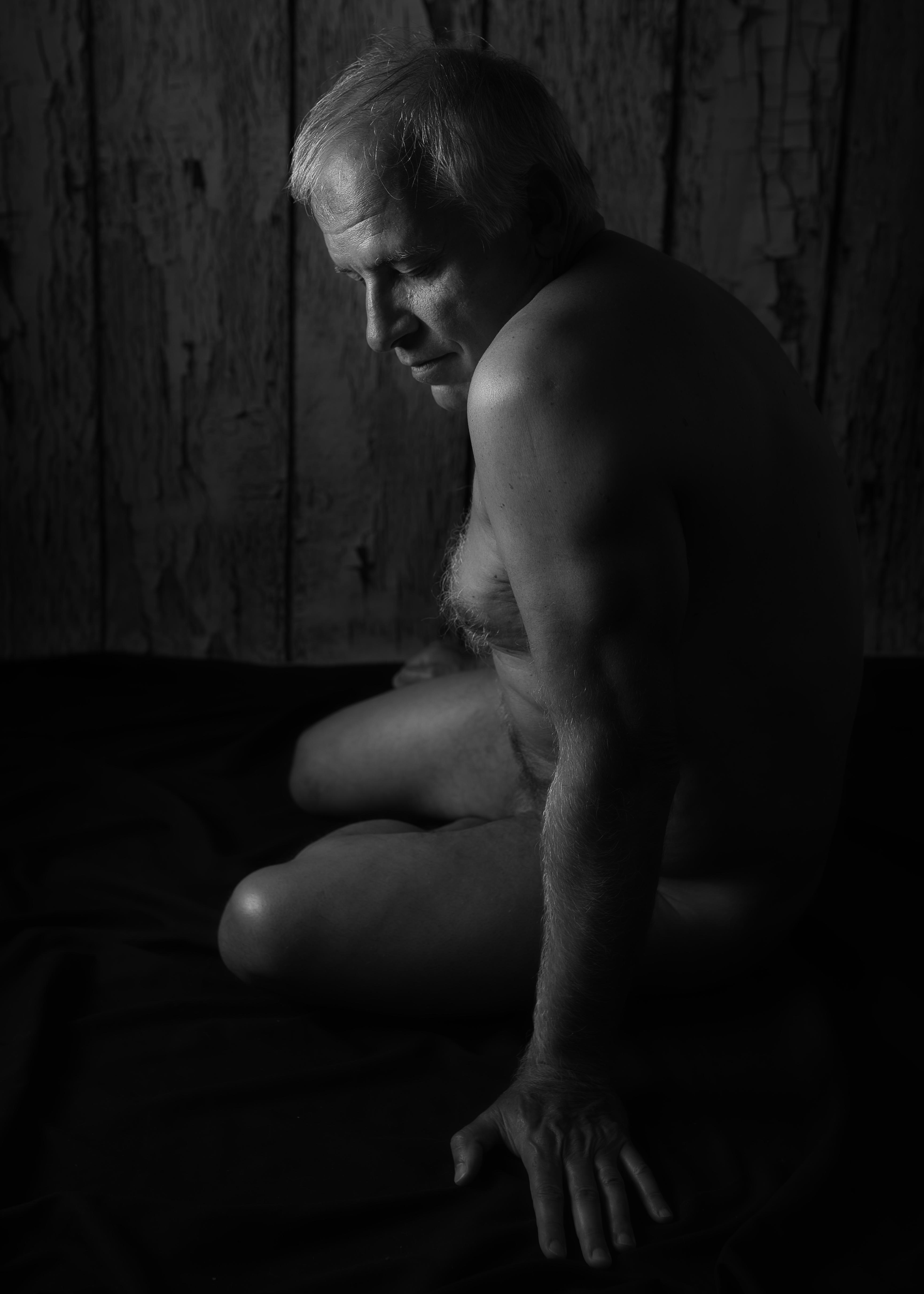 homme mature en nu artistique noir et blanc clair obscur assis au sol