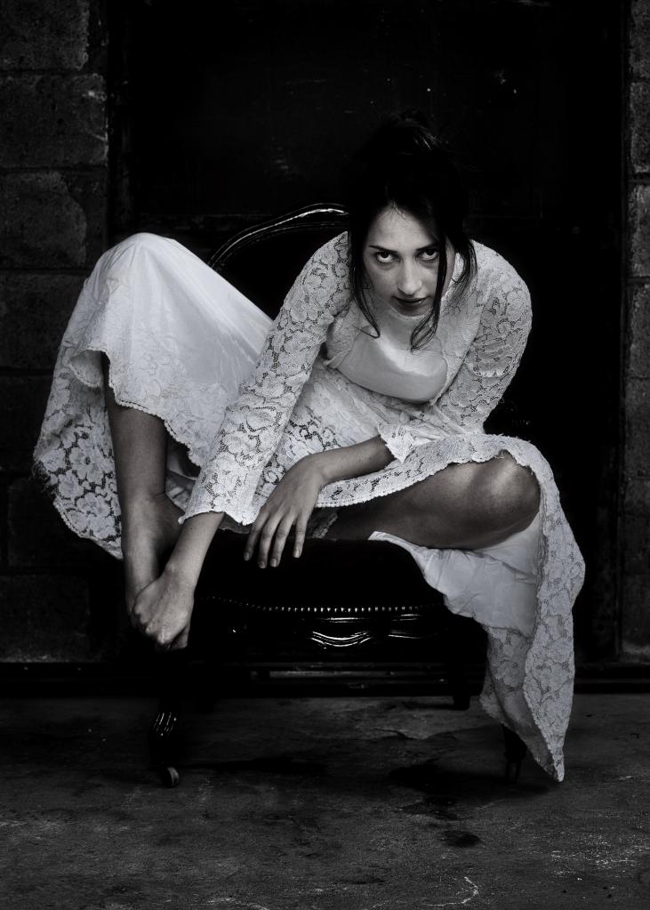 femme en robe de mariée sur un fauteuil ancien le regard noir en noir et blanc