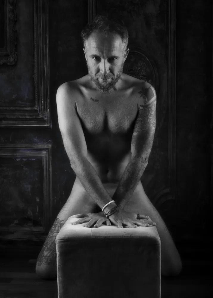 homme tatouée en nu artistique de face les mains sur un tabouret