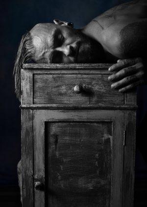 portrait en noir et blanc homme nu la tête rasé sur un meuble vintage