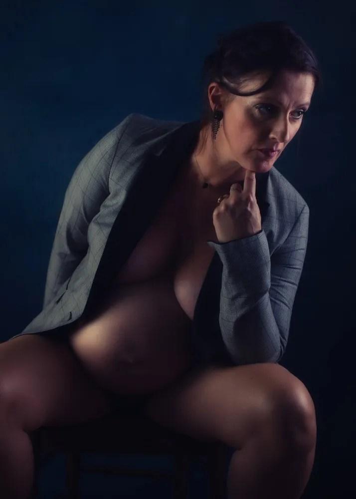femme enceinte en nu artistique dans une veste d'homme l'air pensif