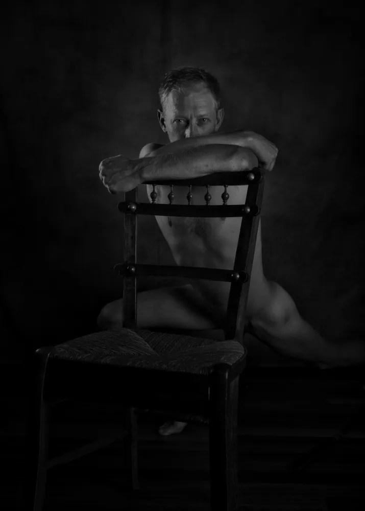 homme en nu artistique accroupi derrière une chaise en bois clair obscur