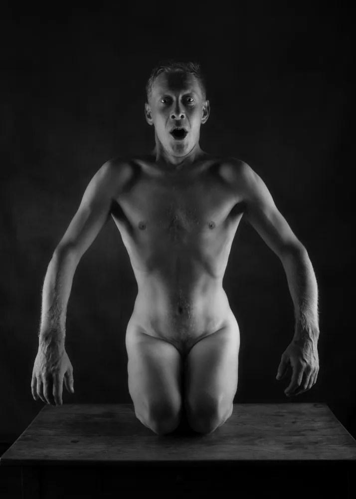 homme en nu artistique à genoux sur une table les bras ouverts et le visage criant
