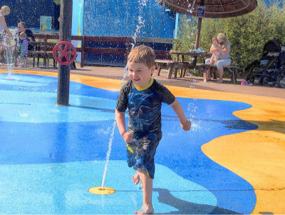 Child running around a wet play area