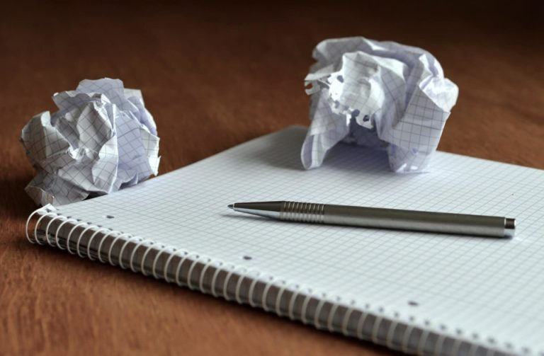 un cuaderno abierto en blanco una pluma y dos hojas listas para tirarlas a la basura